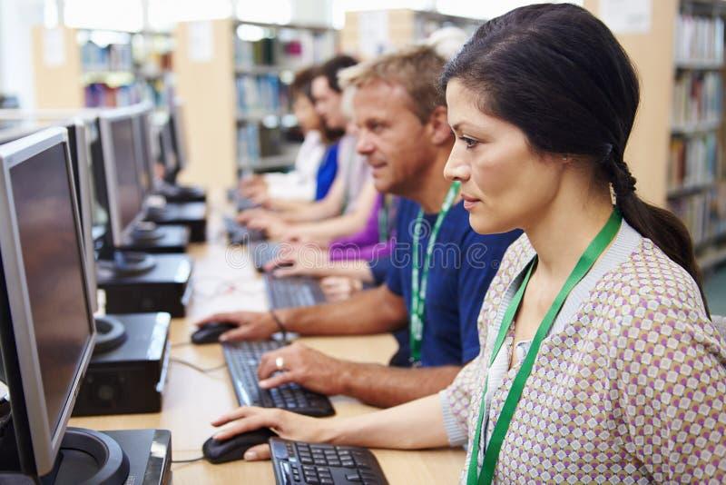 Grupp av mogna studenter som arbetar på datorer arkivfoto