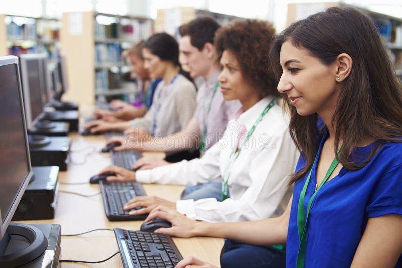 Grupp av mogna studenter som arbetar på datorer arkivfoton