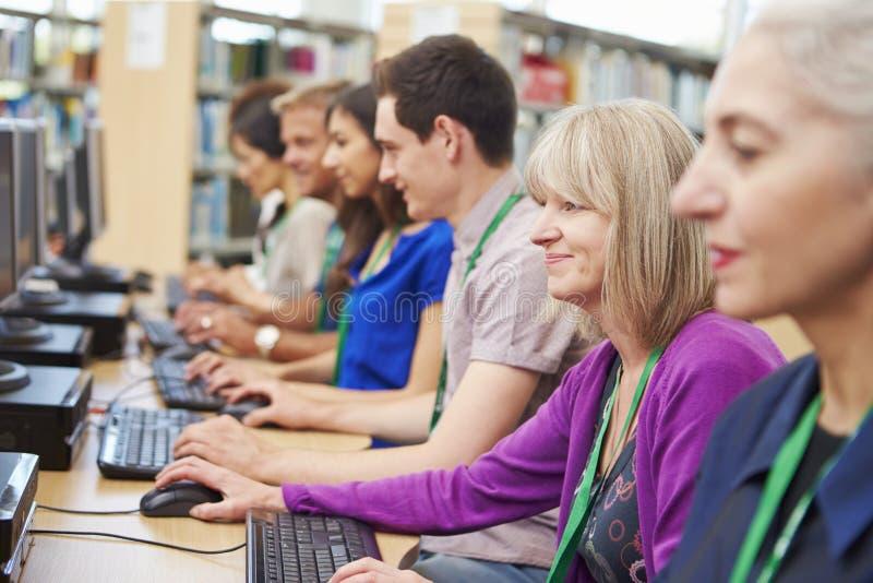 Grupp av mogna studenter som arbetar på datorer royaltyfria foton