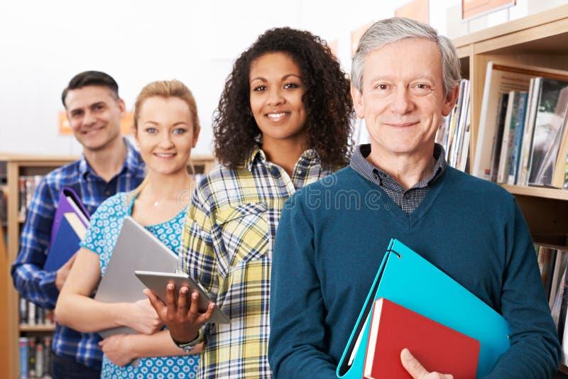Grupp av mogna studenter som studerar i arkiv fotografering för bildbyråer