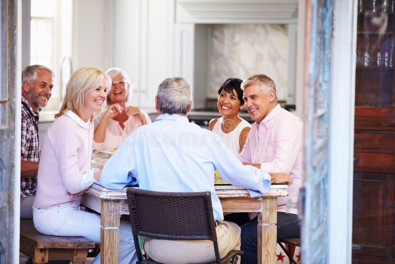 Grupp av mogna vänner som hemma tycker om mål tillsammans royaltyfria bilder