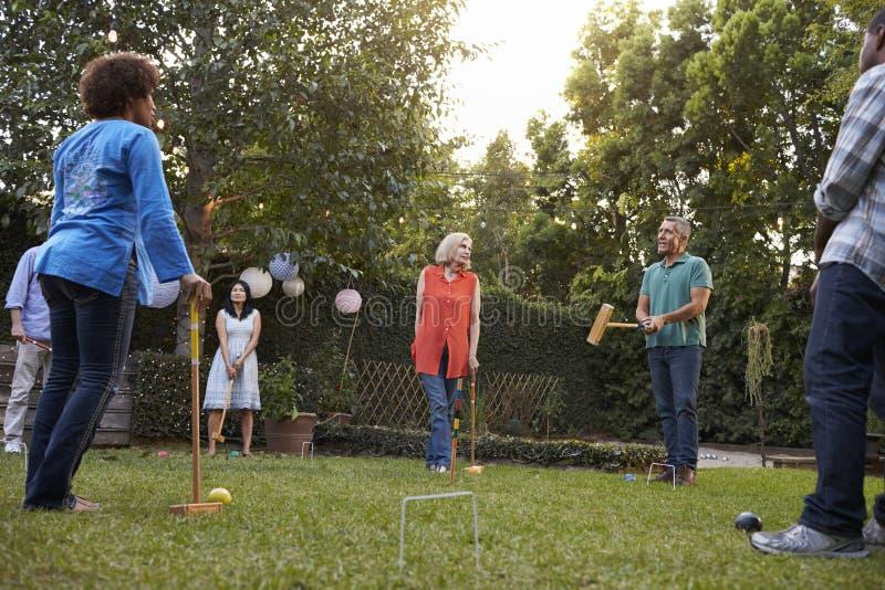 Grupp av mogna vänner som spelar krocket i trädgård tillsammans arkivbild