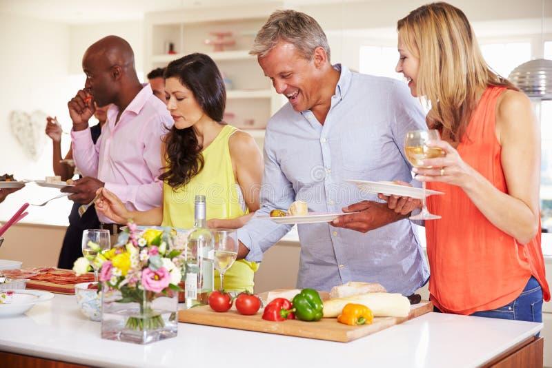 Grupp av mogna vänner som tycker om buffé på matställepartiet royaltyfri fotografi