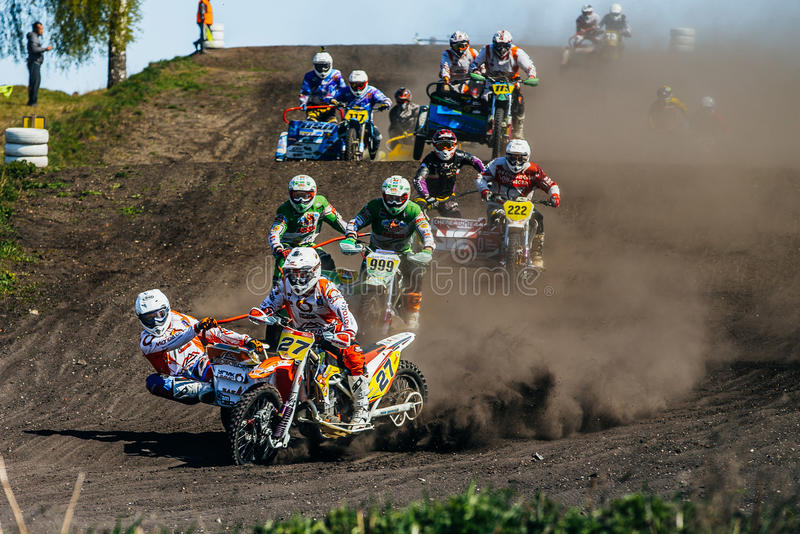 Grupp av motorcyklister med sidecars som rider längs ett dammigt spår royaltyfri foto