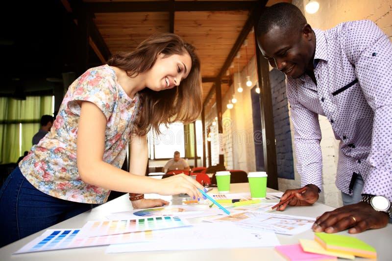 Grupp av multietnisk formgivareidékläckning Unga formgivare som tillsammans arbetar på idérikt projekt arkivbild