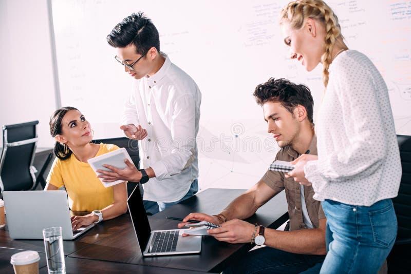 grupp av multietniska affärskollegor som har möte med bärbara datorer och den digitala minnestavlan på modernt arkivfoton