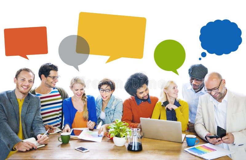 Grupp av multietniska gladlynta formgivare med anförandebubblor arkivbilder