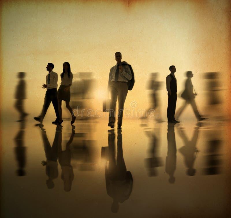 Grupp av näringslivfolk som går vid sidan i solnedgången arkivbild