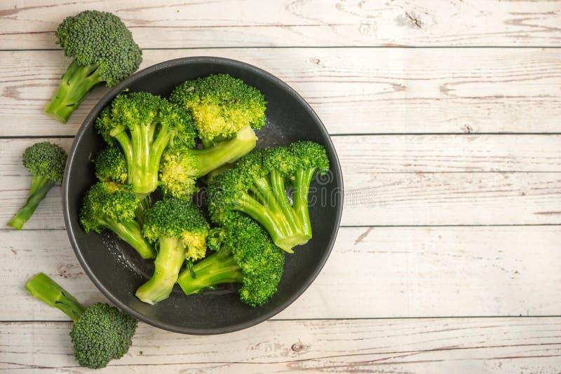 Grupp av ny grön broccoli på den svarta plattan över ljus träbakgrund Top beskådar royaltyfri bild