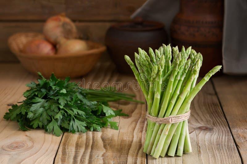 Grupp av ny grön sparris på en trätabell Nya grönsaker i en lantlig inre arkivbild
