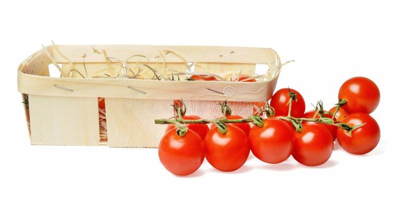 Grupp av nya körsbärsröda tomater och träförpacka för korg Isolerat p? vit Slapp fokus arkivbilder