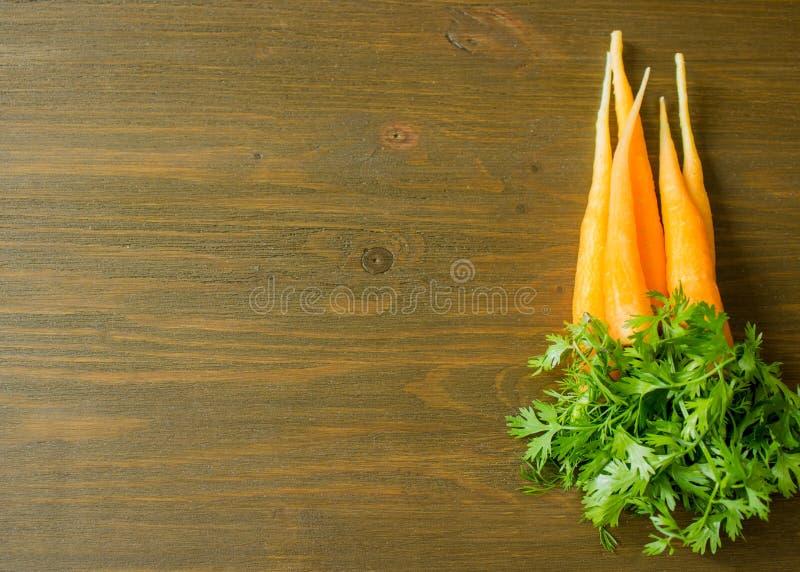 Grupp av nya morötter med gräsplansidor över träbakgrund royaltyfria foton