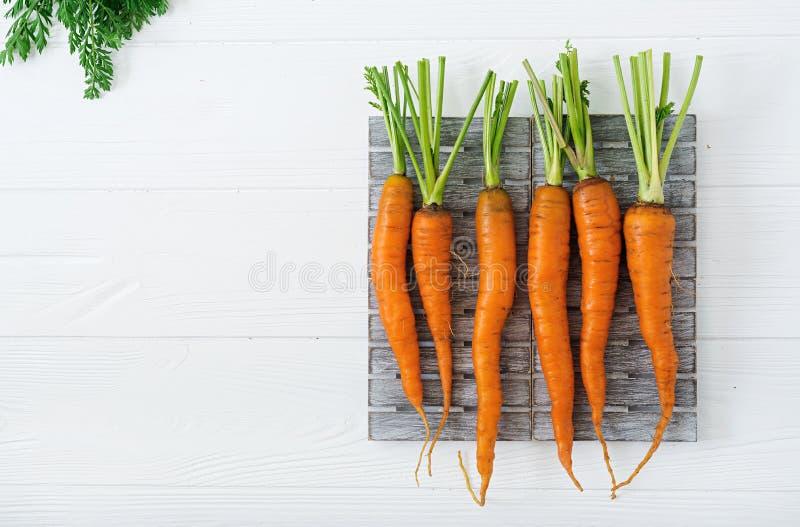 Grupp av nya morötter med gräsplansidor på ljus träbakgrund royaltyfri foto