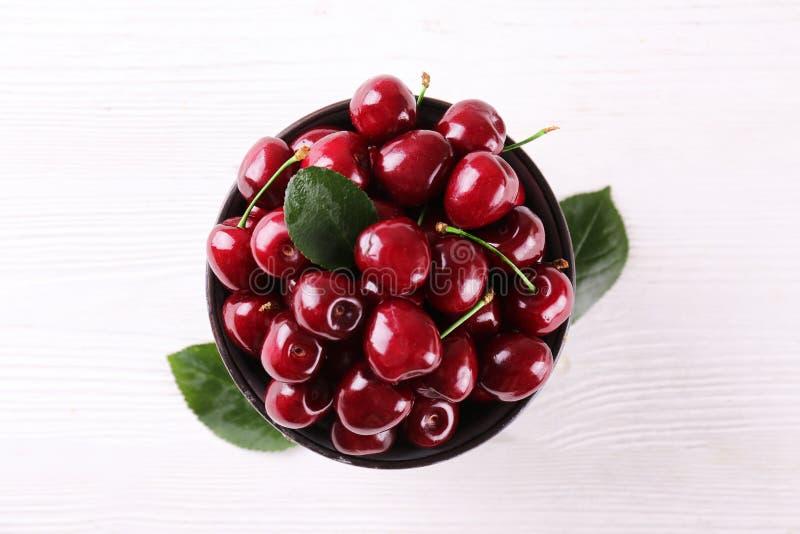 Grupp av nya organiska söta körsbär på texturerad bakgrund r Det sunda n?ringsrika strikt vegetarianmellanm?let som ?r r?tt banta royaltyfria bilder