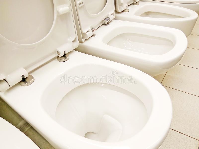 Grupp av nya rena vita öppnade toalettbunkar arkivbilder