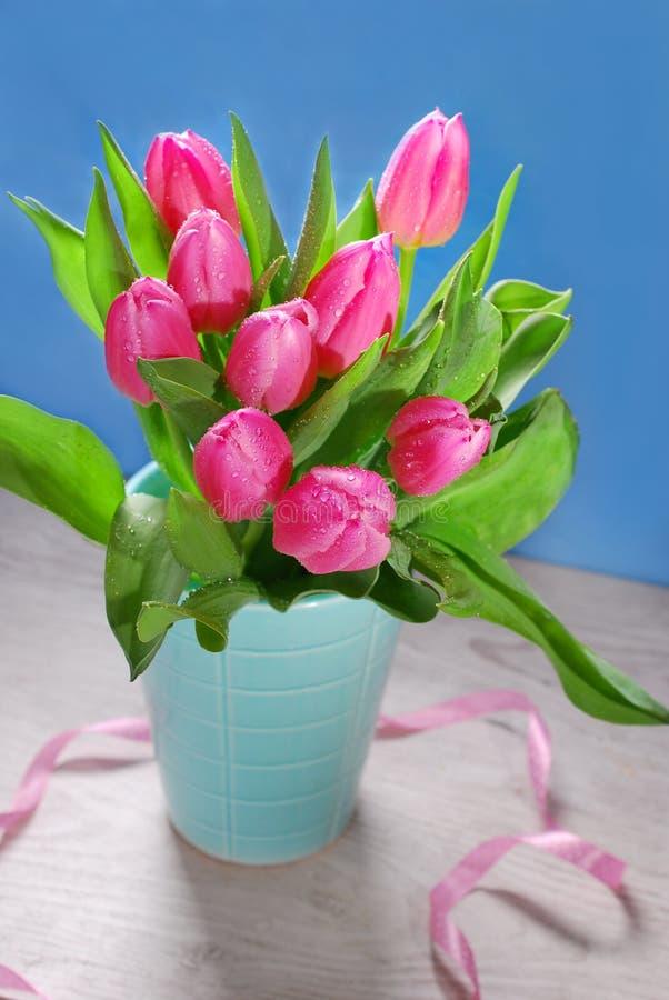 Grupp av nya rosa tulpan i vas arkivfoto