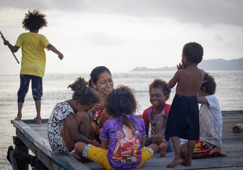 Grupp av okända asiatiska barn som påverkar varandra med den unga vuxna kvinnan på en pir arkivbilder