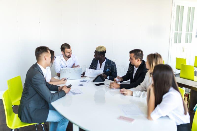 Grupp av olika affärsledare som rymmer ett möte runt om en tabell som diskuterar grafer som visar statistisk analys team arbete arkivfoto