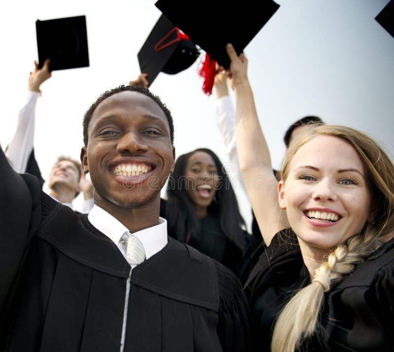 Grupp av olika avlägga examen studenter royaltyfria bilder