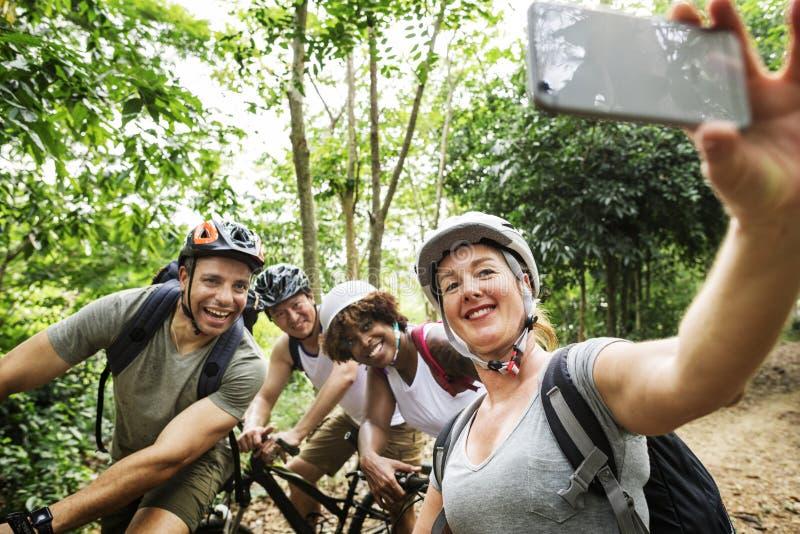 Grupp av olika cyklister i skogen som tar bilden fotografering för bildbyråer