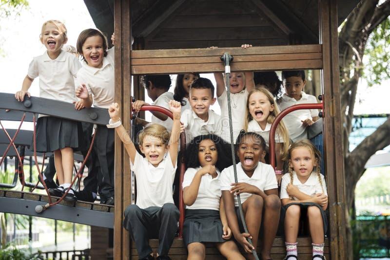 Grupp av olika dagisstudenter på lekplatsen tillsammans arkivfoton
