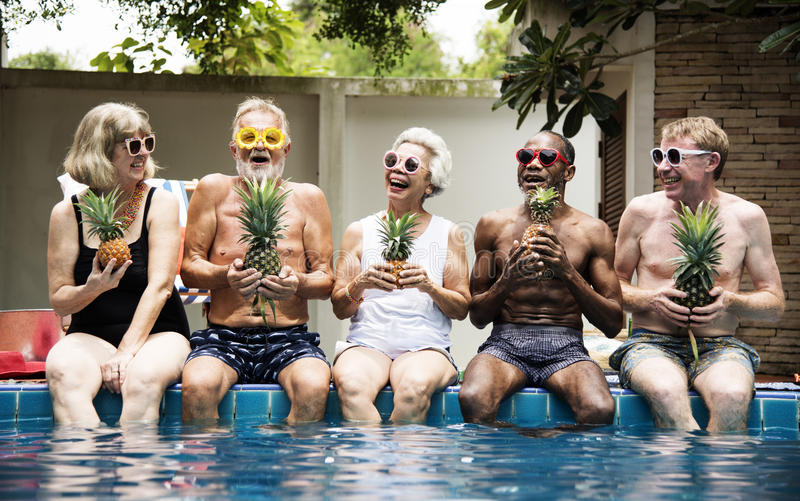 Grupp av olika höga vuxna människor som sitter på den hållande pineaen för poolside fotografering för bildbyråer