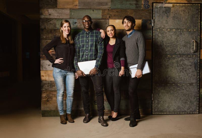 Grupp av olika kollegor som står i ett kontor royaltyfri foto