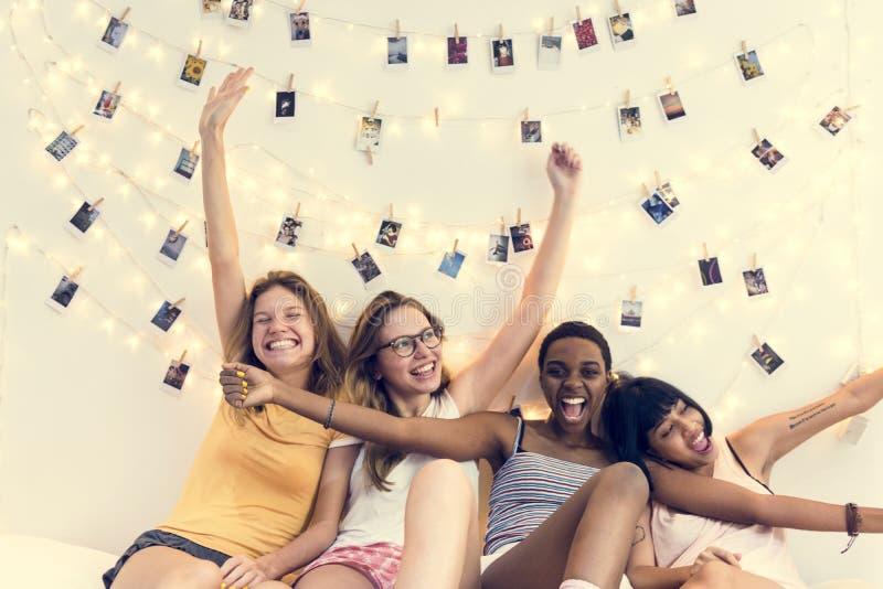 Grupp av olika kvinnor som tillsammans sitter på säng fotografering för bildbyråer