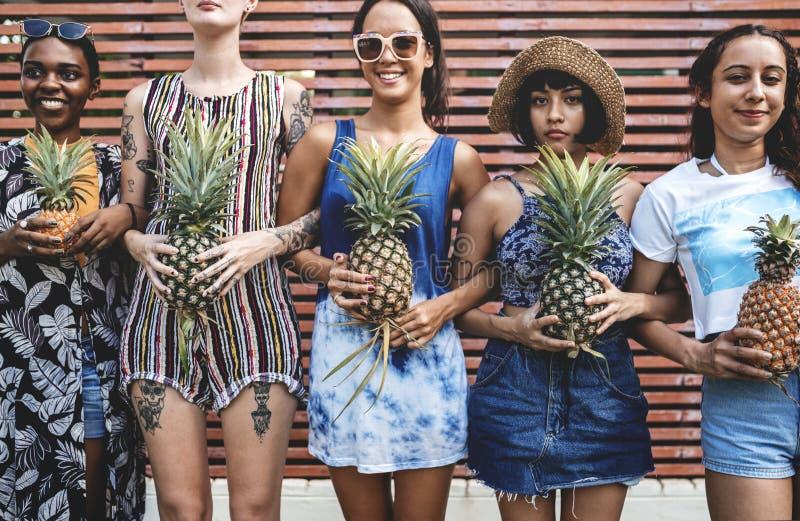 Grupp av olika kvinnor som tillsammans står hållande ananas arkivfoto