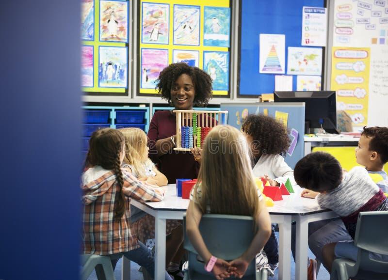 Grupp av olika studenter på daycare arkivbilder