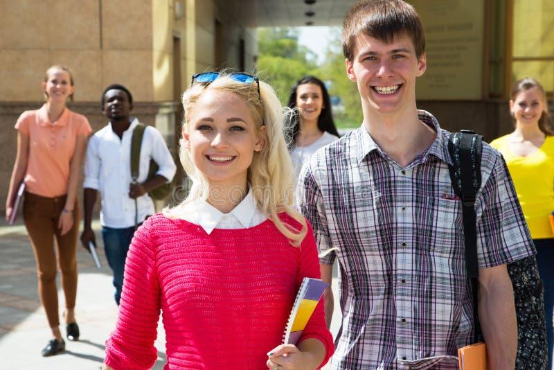 Grupp av olika studenter som tillsammans går arkivbild