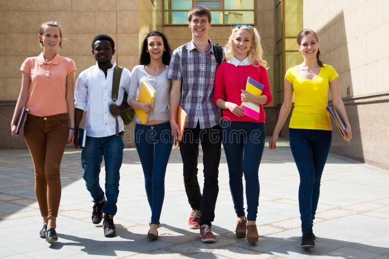 Grupp av olika studenter som tillsammans g?r arkivbilder