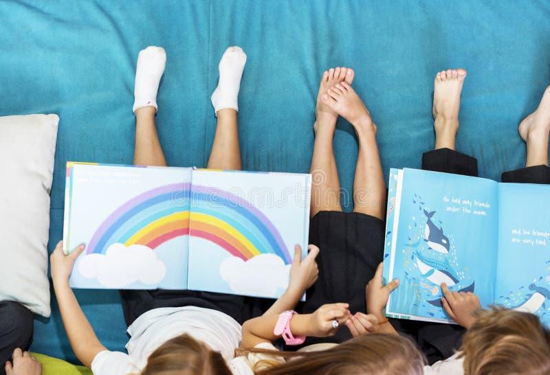 Grupp av olika unga studenter som läser barnberättelseboken Toge royaltyfria bilder