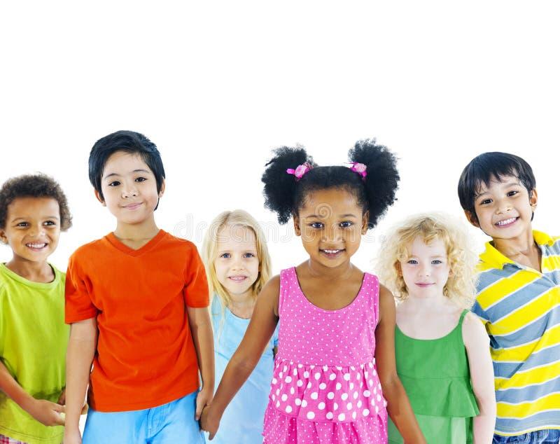 Grupp av olika ungar som rymmer händer fotografering för bildbyråer
