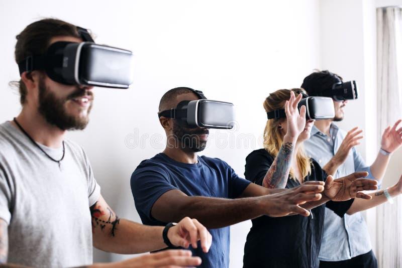 Grupp av olika vänner som erfar virtuell verklighet med VR-hörlurar med mikrofon fotografering för bildbyråer