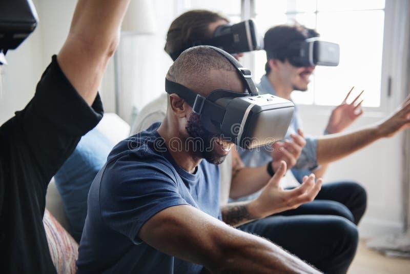 Grupp av olika vänner som erfar virtuell verklighet med VR-hea arkivfoton