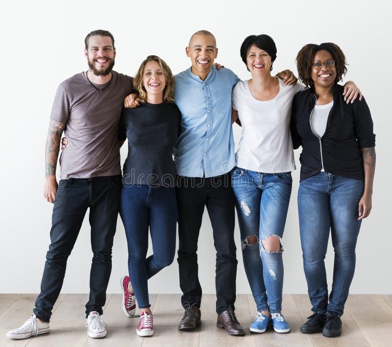 Grupp av olika vänner som tillsammans ler och kramar fotografering för bildbyråer