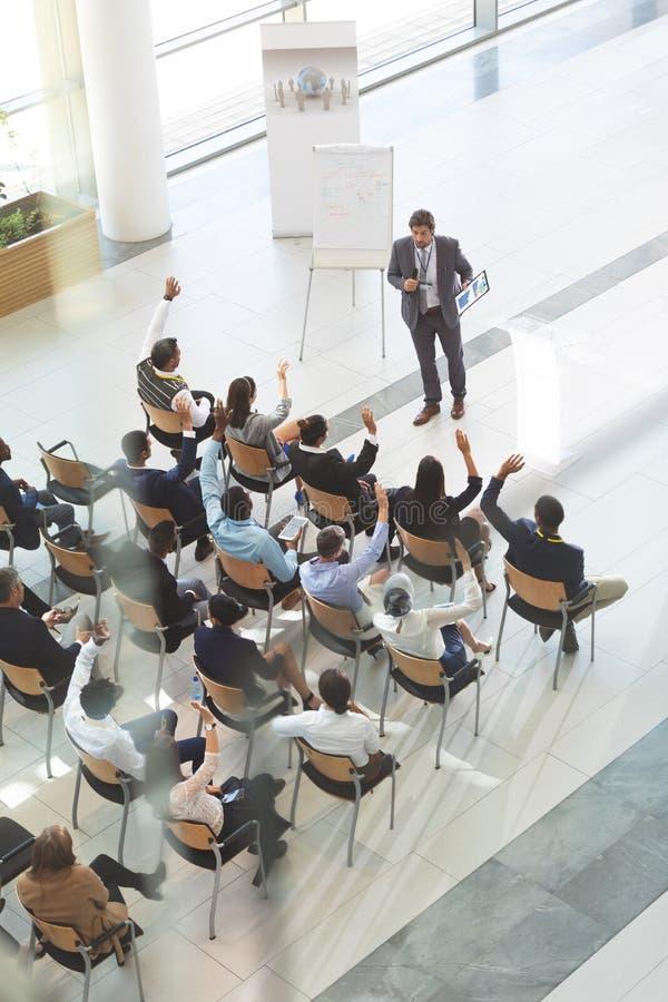 Grupp av olikt affärsfolk som lyfter deras händer för att fråga frågor till affärsmannen på konferensen arkivbilder