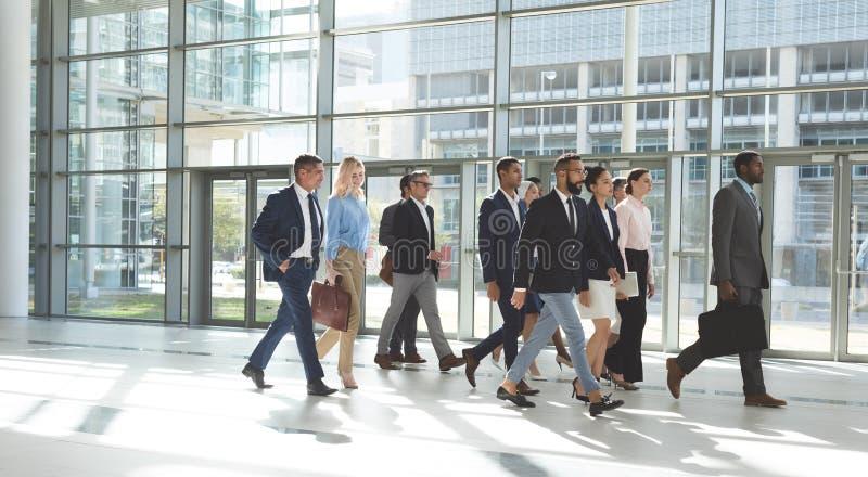 Grupp av olikt affärsfolk som tillsammans går i lobbykontor royaltyfria foton