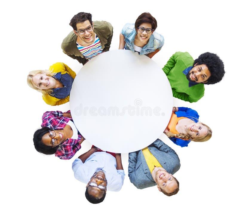 Grupp av olikt folk som bär en vit cirkel fotografering för bildbyråer