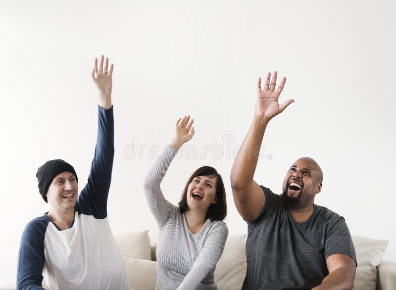 Grupp av olikt folk som lyfter deras händer royaltyfri bild