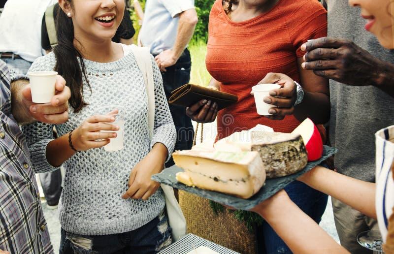 Grupp av olikt folk som testar ost på matstallen royaltyfri foto