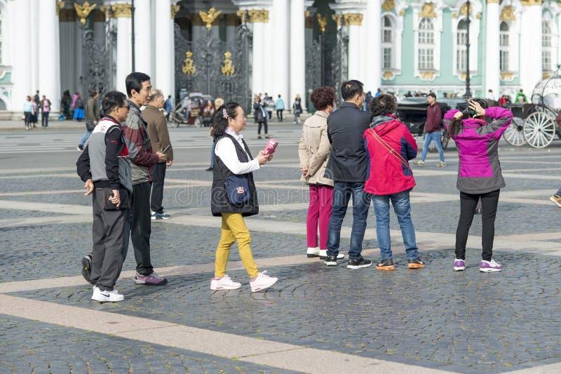 Grupp av orientaliska turister av det asiatiska utseendet på slottfyrkanten av St Petersburg på bakgrunden av eremitboningen, Rys royaltyfria bilder