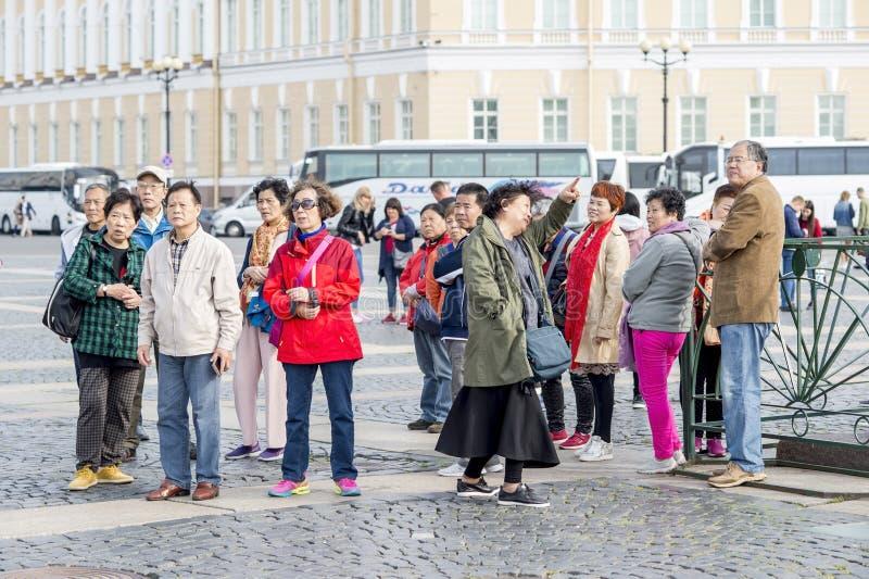 Grupp av orientaliska turister av det asiatiska utseendet på slottfyrkanten av St Petersburg på bakgrunden av vita turist- bussar royaltyfria bilder