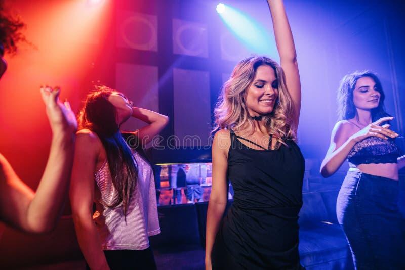Grupp av partifolk som dansar i ett disko royaltyfri fotografi