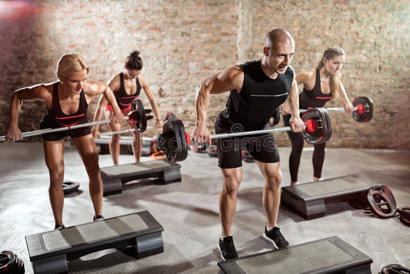 Grupp av passformfolk som gör övning med vikter arkivfoton