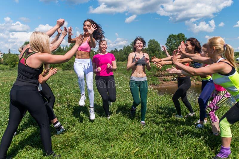 Grupp av passformwomemlöpare som avslutar att applådera för folk arkivfoto