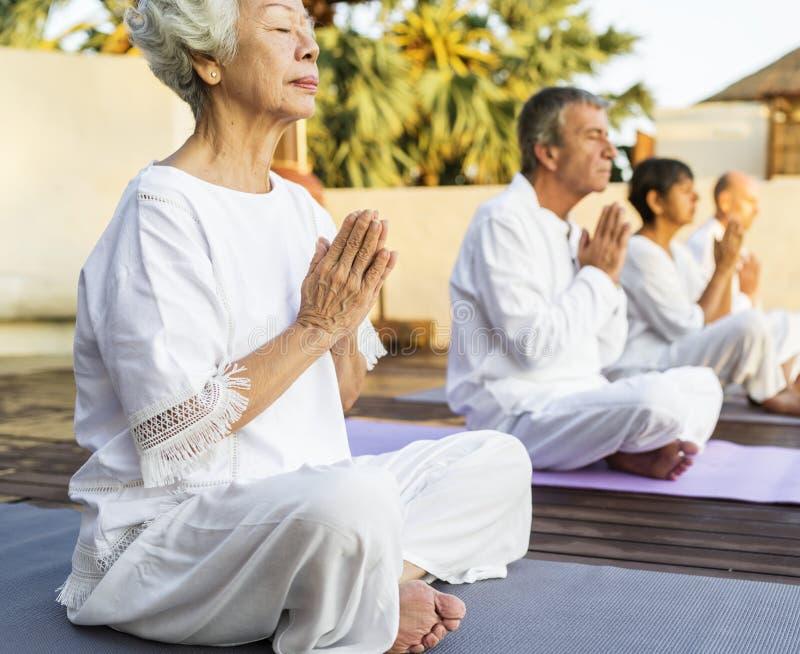 Grupp av pensionärer som öva yoga i morgonen royaltyfria foton