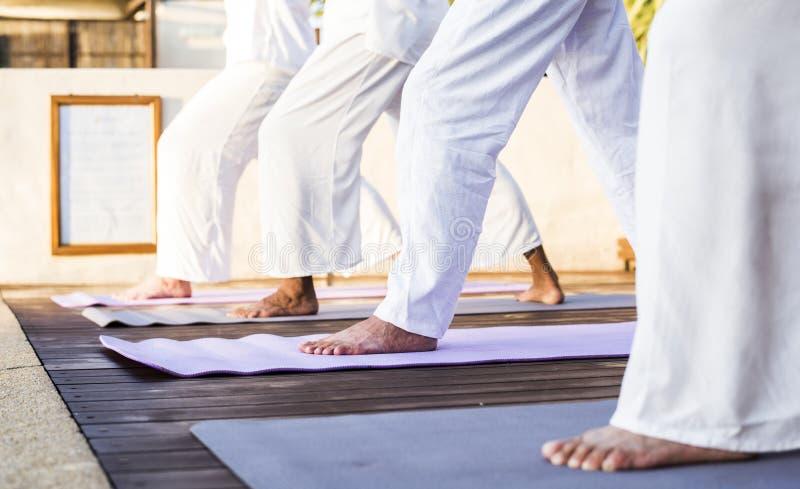 Grupp av pensionärer som öva yoga i morgonen arkivbild