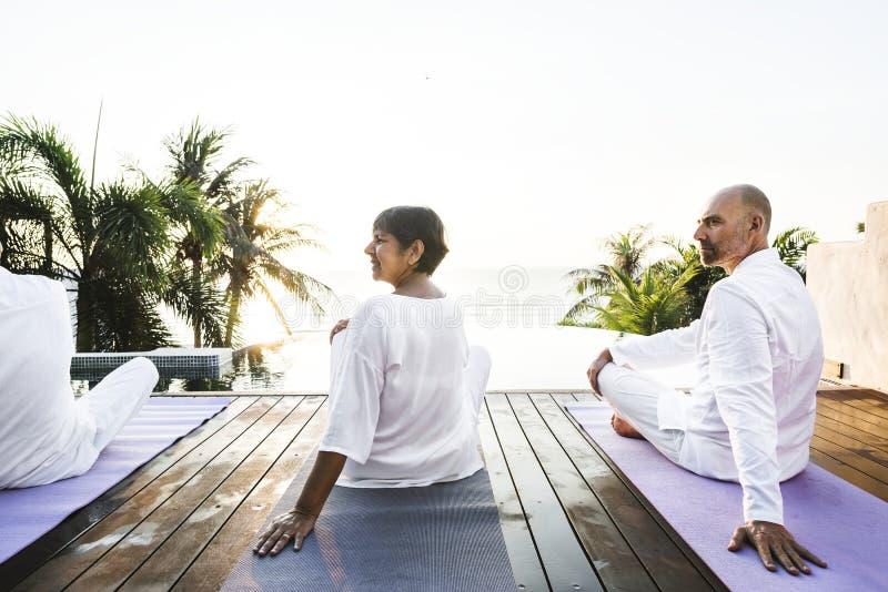 Grupp av pensionärer som öva yoga vid pölen arkivbilder